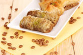 Sweet baklava on plate on wooden background — Stock Photo