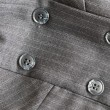 Button on a gray suit — Stock Photo