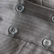 Button on gray suit — Stock Photo #11788763