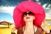 Mädchen am strand in einen roten hut, eine große gläser — Stockfoto