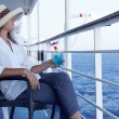 A woman in a hat and a cocktail  on the liner - Stock Photo