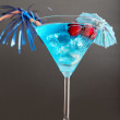 Blue cocktail with ice and umbrella — Stock Photo