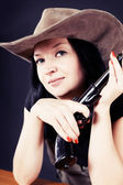 Pretty girl in a hat with a gun — Stock Photo