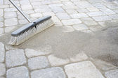 Broom Sweeping Sand into Pavers — Stock Photo