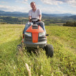 Man riding a lawn tractor — Stock Photo