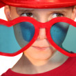 Royalty-Free Stock Photo: Boy Peeking Hesitantly Over Heart-Shaped Glasses