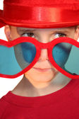Boy Peeking Hesitantly Over Heart-Shaped Glasses — Stock Photo