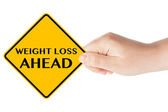 Weight Loss ahead traffic sign with hand — Stock Photo