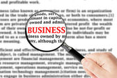 Förstoringsglas och business tecken — Stockfoto