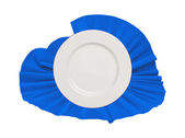 White plate on blue cloth isolated on white — Stock Photo