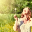 Beautiful girl with dandelion enjoying the summer sun - Stock Photo