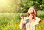 Beautiful girl with dandelion enjoying the summer sun — Stock Photo
