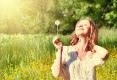 Beautiful girl with dandelion enjoying the summer sun — Stock Photo