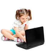 Little girl sitting at the computer — Stock Photo