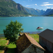 Wood sheds on the shore of fjord. - Stock Photo