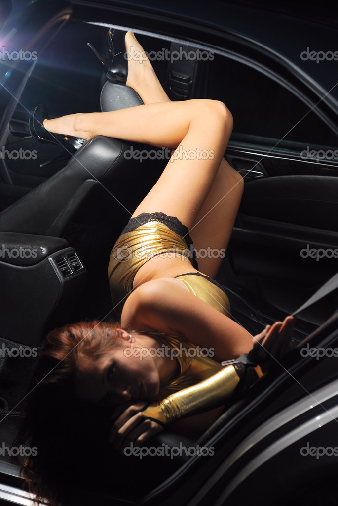 Young woman is lying on the leather back seat of auto. She is wearing shining suit with lace. Her slender legs are placed on front seat back. — Stock Photo #10827041