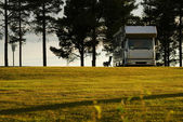 Mobile home on camping site into the sunset. — Stock Photo