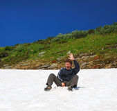 Tourist sliding on the snowfield in summer. — Stock Photo