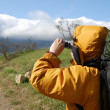 Stock Photo: Hiker filming scenery.
