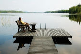 Lake with wooden platform and woman resting. — Stock Photo