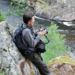 Man with camera on the rock over mountain river. - Stock Photo