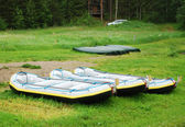Rafts and canoes in the green glade. — Stock Photo