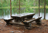 Timber table with benches near taiga river — Stock Photo