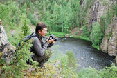 Happy man with camera on the top of taiga forest. — Stock Photo