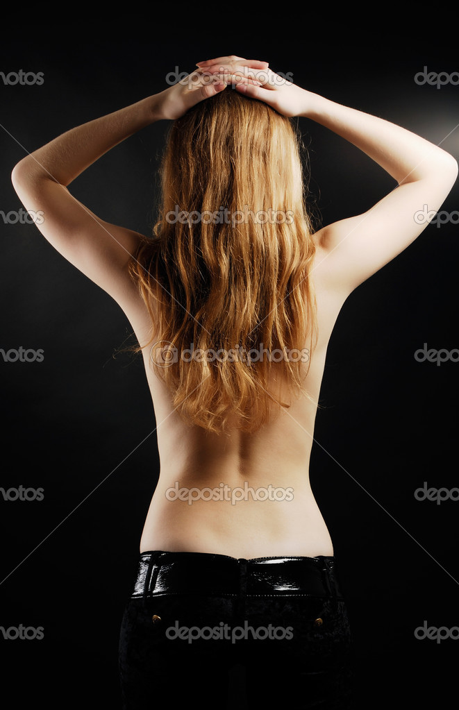 Blonde woman is standing from back in the black background. She is topless. She is wearing only black pants. She is putting her arms on her head. — Stock Photo #11112132