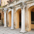 Ancient columns near old building with arches — Stock Photo
