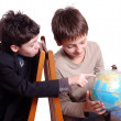 Stock Photo: Two boys researching sphere isolated on white