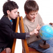 Stock Photo: Two boys researching globe isolated on white