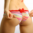 Female hands settle swimming trunks on seductive buttocks — Stock Photo #11203102