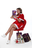 Woman dressed as Mrs. Claus holding a present — Stock Photo