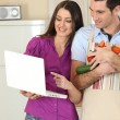 Couple in kitchen with computer and vegetables — Stock Photo