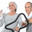 Elderly couple working out together in gym — Stock Photo