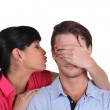 Young woman kissing her boyfriend on the cheek hiding his eyes — Stock Photo #10832658