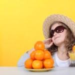 Little girl with freshly squeezed orange juice — Stock Photo