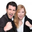 Business couple with their fists in the air - Stock Photo