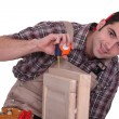 Tradesman using a measuring tape - Stock Photo