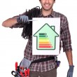 Electrician holding energy information board — Stock Photo