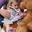 Young girl listening to her teddy's heartbeat — Stock Photo