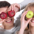 Man and woman covering her eyes with apples — Stock Photo