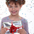 Little girl receiving birthday present - Stock Photo