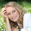 Blond woman laying in a field of daisies — Stock Photo