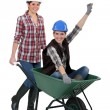 Craftswoman carrying a colleague sitting in a wheelbarrow — Stock Photo #10837441