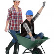 Craftswoman carrying a colleague sitting in a wheelbarrow — Stock Photo