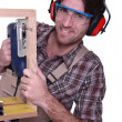 Stock Photo: Carpenter sawing wooden frame