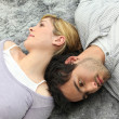 Couple lying on carpet — Stock Photo #10838983