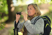 Woman with rucksack and binoculars — Stock Photo